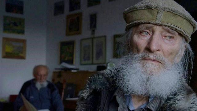 Starsi mężczyźni w pokoju, jeden patrzy za okno, na ścianach obrazy