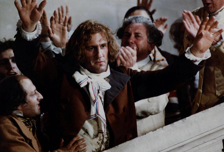 """Kadr zfilmu """"Danton"""". Mężczyźni wstrojach zepoki podnoszą dłonie wgeście głosowania."""