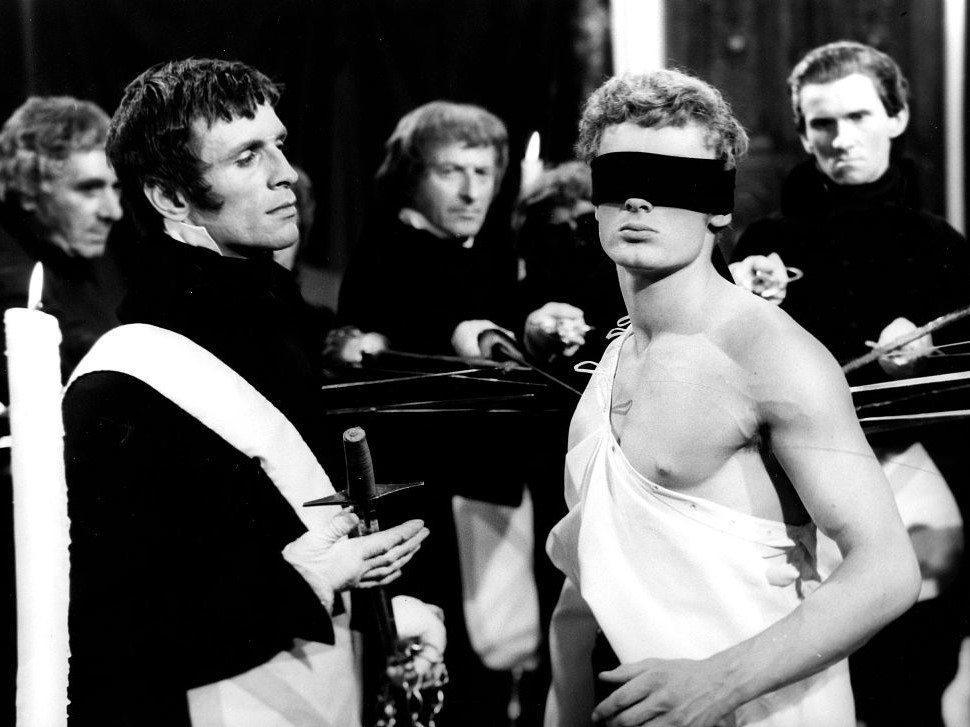 """Kadr zfilmu """"Popioły"""". Mężczyzna osłonięty częściowo białym płótnem izczarną opaską naoczach odwraca głowę, wokół niego stoją mężczyźni wmundurach."""