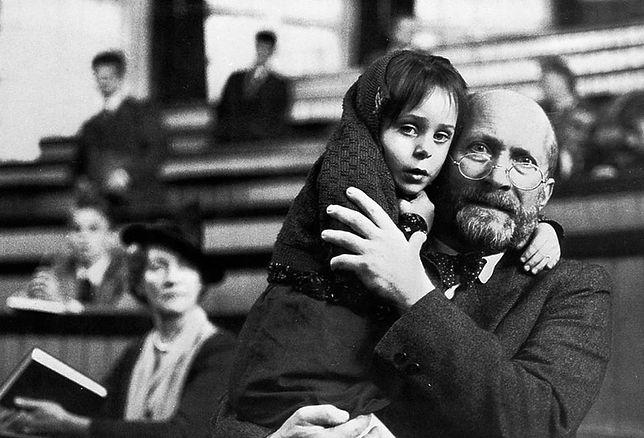 """Kadr zfilmu """"Korczak"""", nazdjęciu mała dziewczynka przytula się doKorczaka, ten przytula ją wgeście obrony. Ztyłu ławki, wniektórych ludzie."""