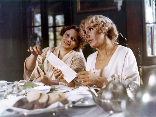 """Kadr zfilmu """"Panny zwilka"""". Nazdjęciu dwie kobiety siedzące przy stole, jedna wrękach ma list, druga nachyla się doniej coś mówiąc."""