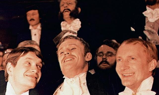 """Kadr zfilmu """"Ziemia obiecana"""". Nazdjęciu kilkoro mężczyzn ubranych elegancko, śmiejących się."""