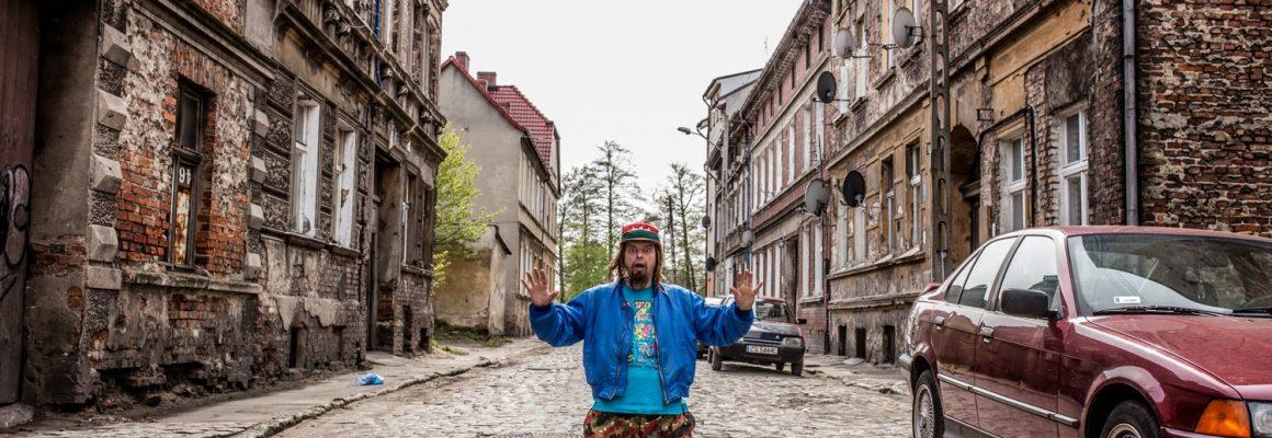 Kolorowe zdjęcie, mężczyzna klęczący na bruku, po obu stronach zaniedbane kamienice