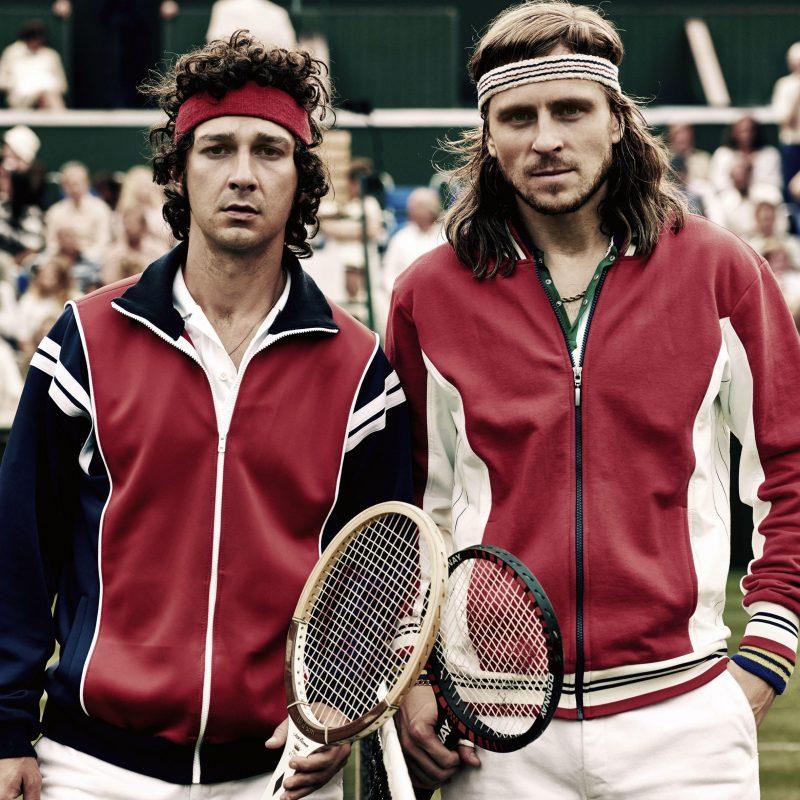 """Bohaterowie filmu """"Borg/McEnroe. Między odwagą a szaleństwem"""" na fotosie filmowym - ubrani jak tenisiści stoją na korcie."""