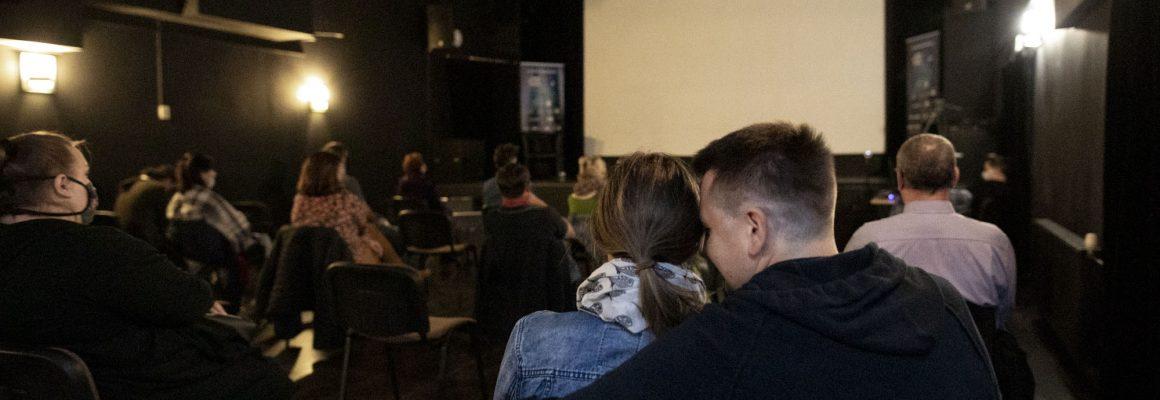 Ludzie siedzący przed ekranem w Klubie Delta