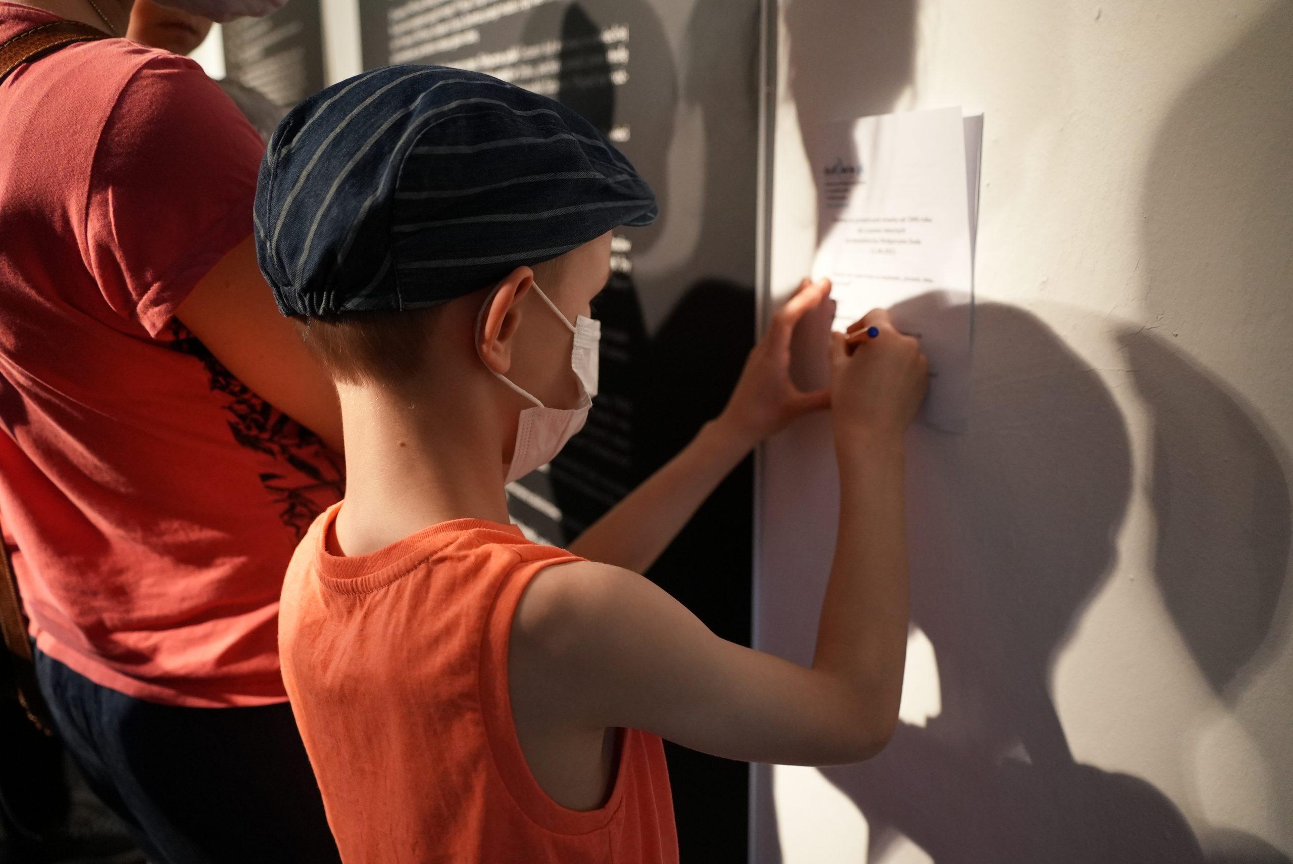 Chłopiec zapisuje coś nakartce