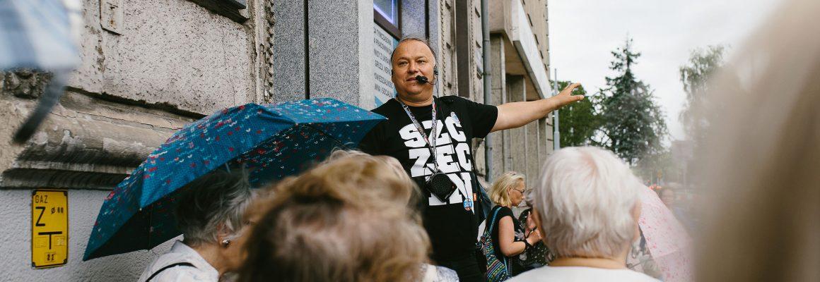 Przewodnik Tomasz Wieczorek opowiada historie uczestnikom spaceru