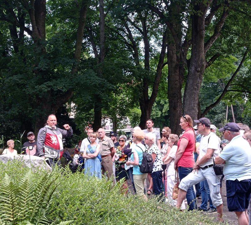 Grupa uczestników spaceru stoi w parku i słucha przewodnika, Tomasza Wieczorka