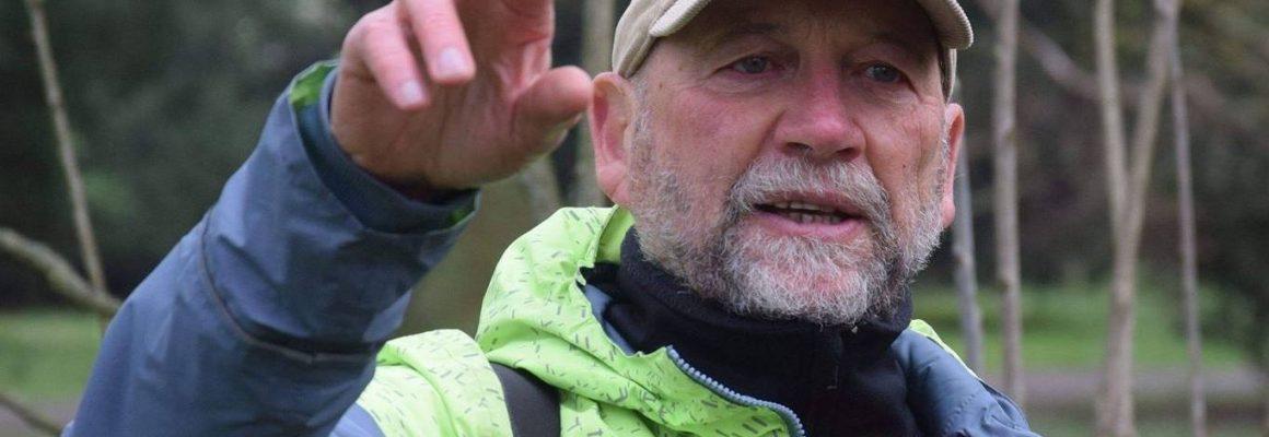 Paweł Madejski na tle drzew wskazuje uczestnikom spaceru coś poza kadrem