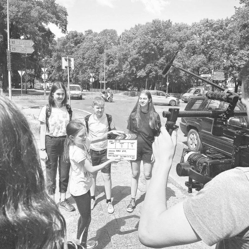 """Młodzi uczestnicy warsztatów na ulicy podczas kręcenia filmu """"13:13"""""""